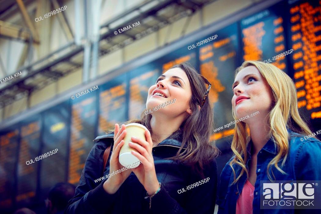Stock Photo: Women looking at departure information, London, UK.