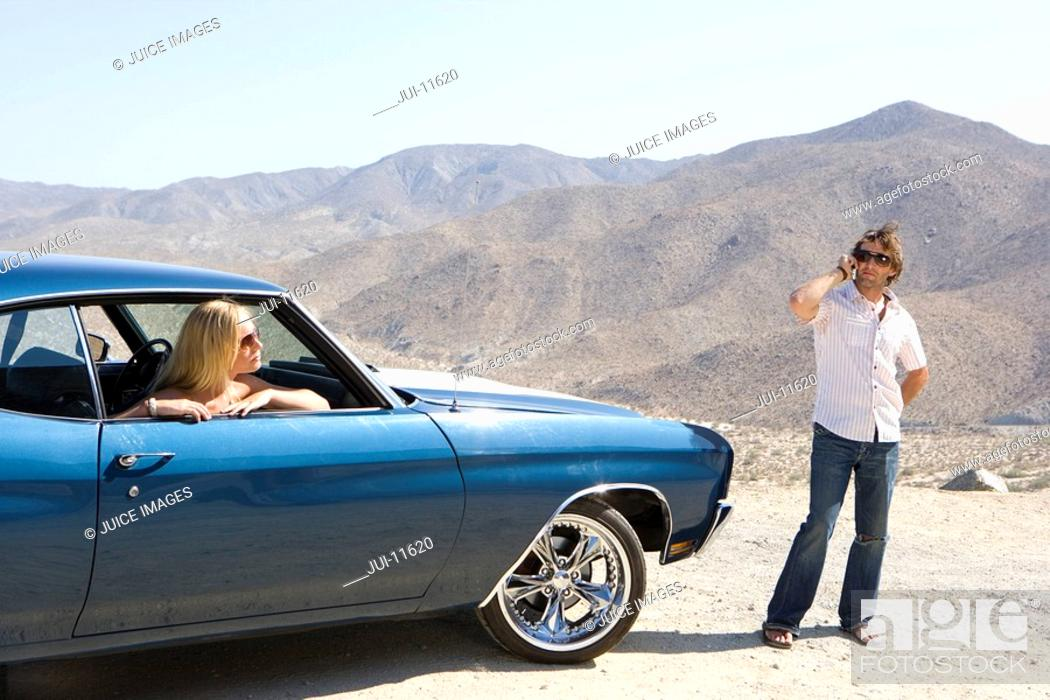 Stock Photo: Young woman in car looking out window at man using mobile phone by car in desert.