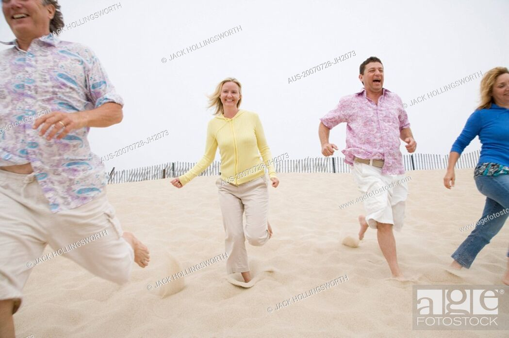 Stock Photo: Two couples running on the beach.