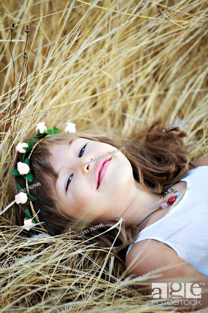 Stock Photo: Portrait of a young girl laying in the countryside.