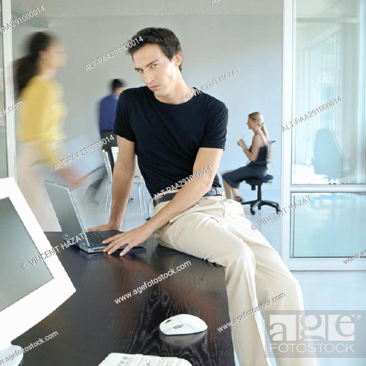 Stock Photo: Man sitting on edge of desk in busy office.