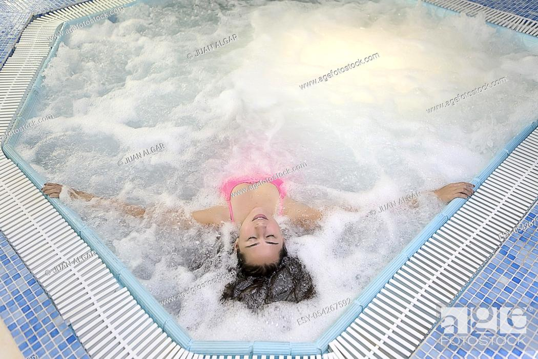 Stock Photo: From above�young girl with eyes closed taking rest in the hydrotherapy pool. Horizontal indoors shot.