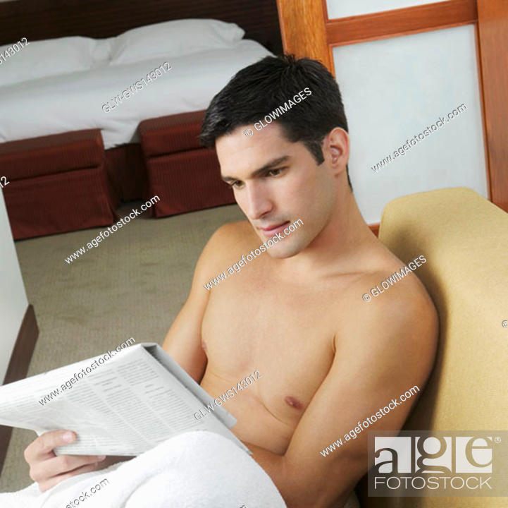 Stock Photo: High angle view of a young man reading a newspaper.