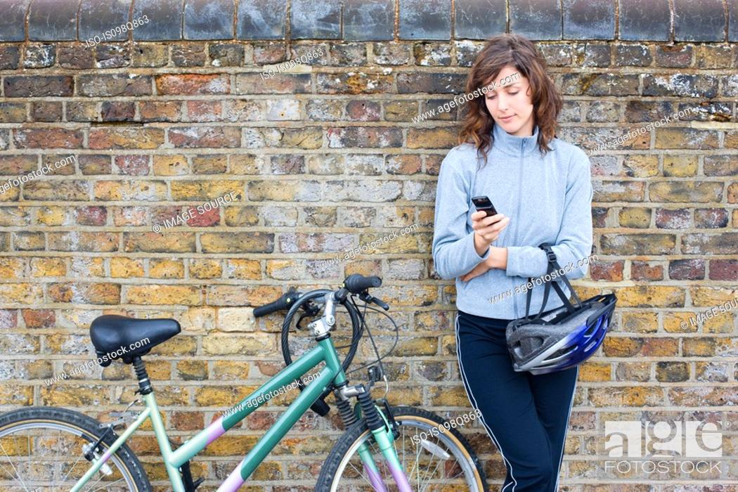 Stock Photo: Woman with bike and cellphone.