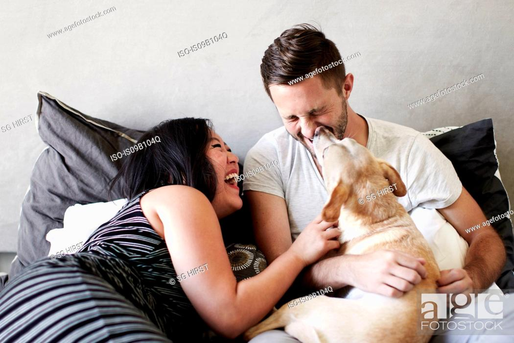 Stock Photo: Couple reclining on bed playing with dog.