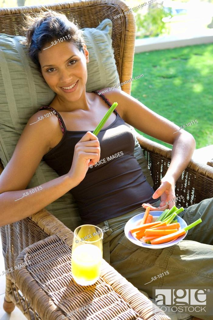 Stock Photo: Young woman in armchair outdoors with plate of vegetable sticks, smiling, portrait.