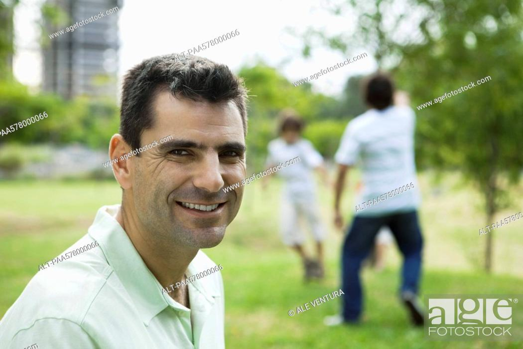 Stock Photo: Man smiling at camera, sons playing in background.