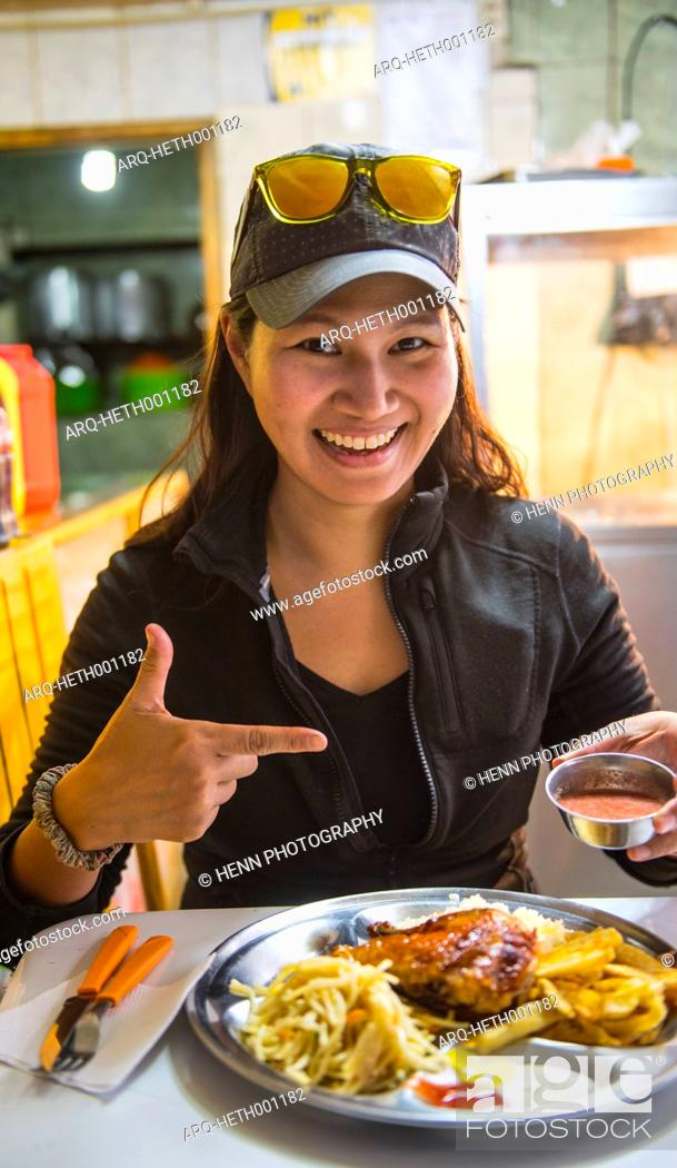 Stock Photo: Smiling woman eating street food in Potosi, Tomas Frias Province, Bolivia.
