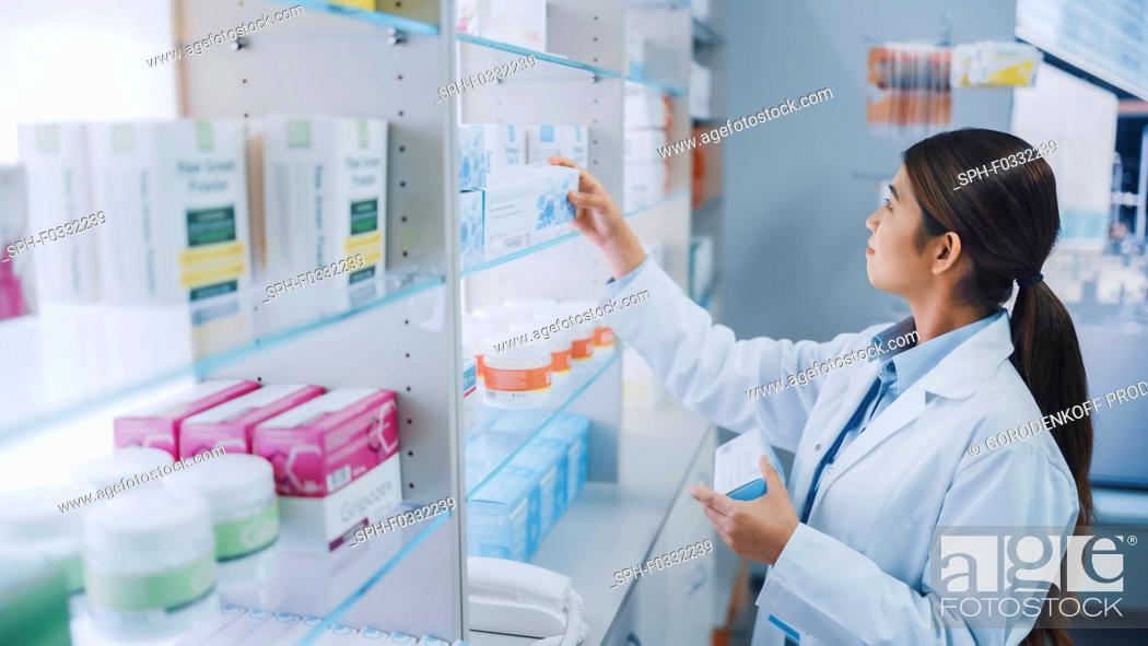 Stock Photo: Pharmacist arranging medication on shelves.