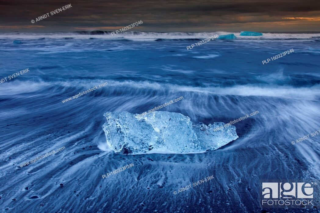 Stock Photo: Melting block of ice washed on beach along the Atlantic Ocean coastline at Breidamerkursandur black sands in winter, Sudursveit, Iceland.