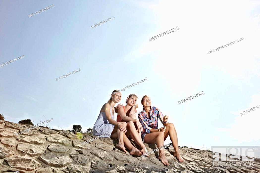 Stock Photo: Germany, Cologne, Young women sitting on rivernbank.