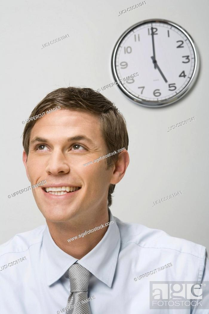 Stock Photo: Businessman next to wall clock.