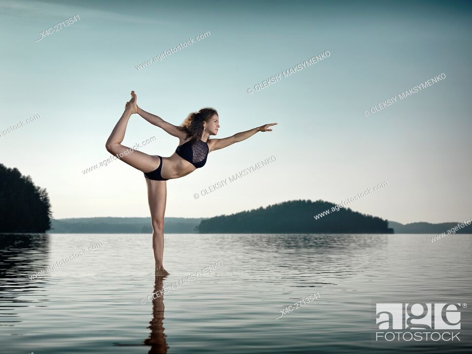 Stock Photo: Young woman practicing Hatha yoga on a floating platform in water on the lake during sunrise in the morning. Yoga Dancer posture, Dandayamana Dhanurasana.