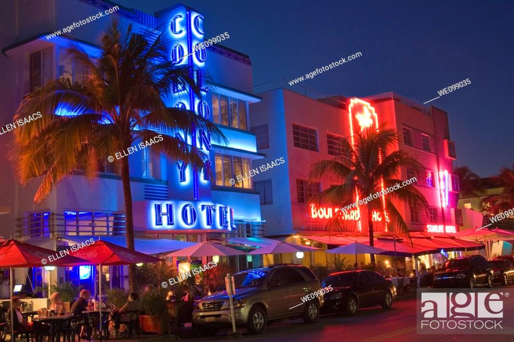 Stock Photo: Art deco hotels at night with neon lights along Ocean Drive, in the Art Deco District of South Beach, Miami, Florida  People are eating at the sidewalk.