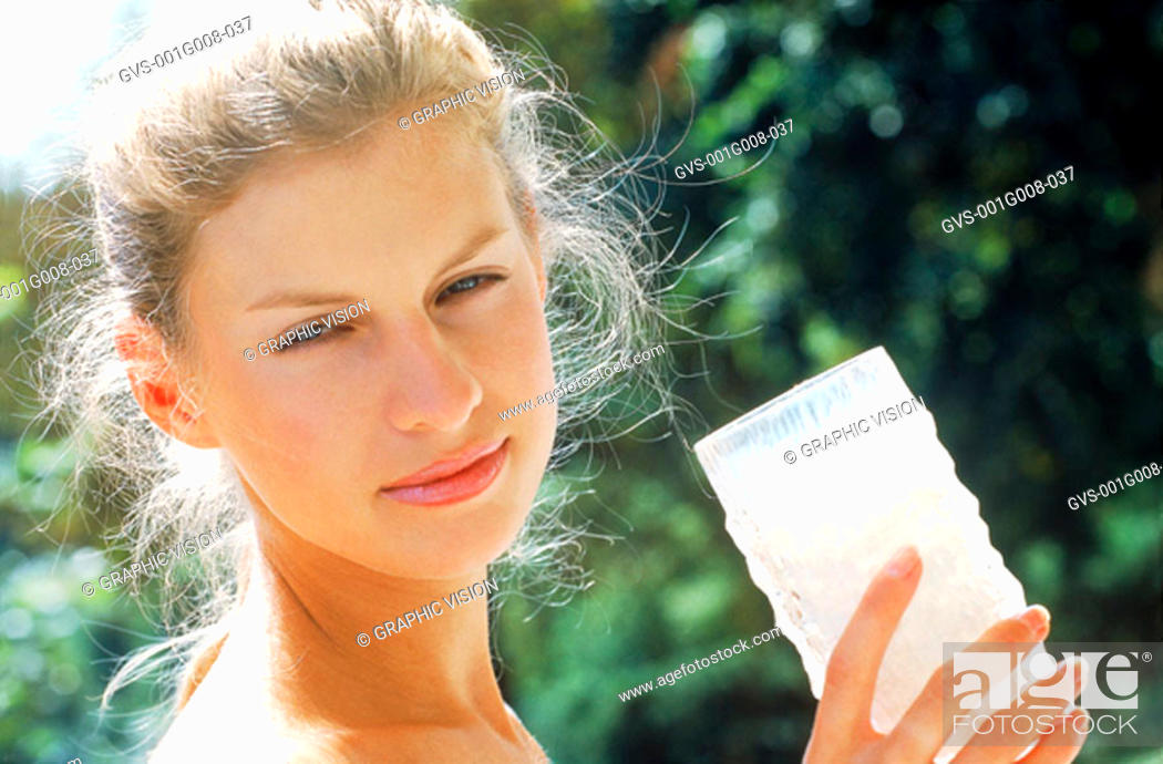 Stock Photo: Young woman holding glass of milk.