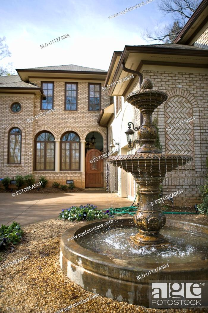Stock Photo: Outdoor front view of affluent home with fountain.