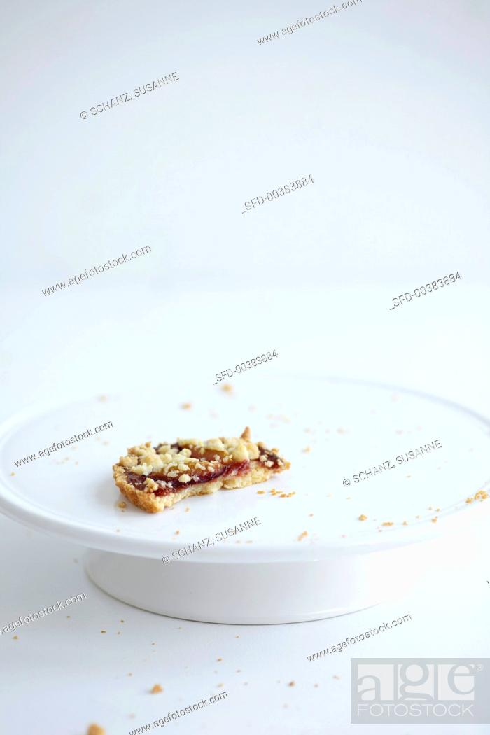 Photo de stock: The remains of a damson crumble cake on a cake stand.