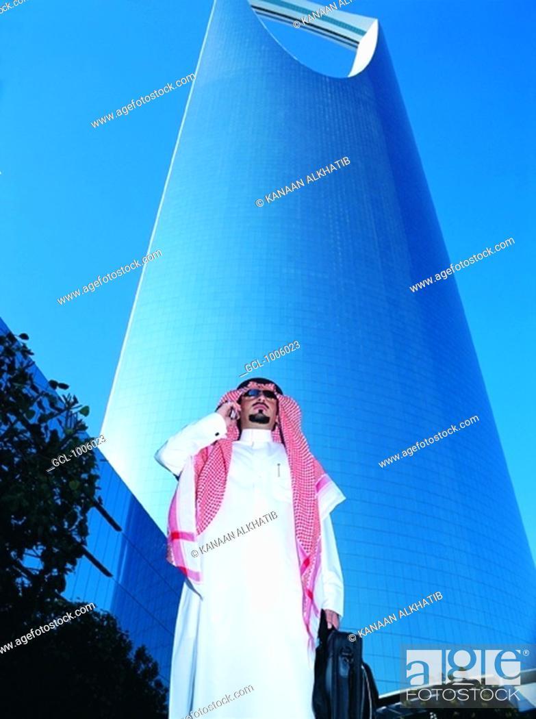 Stock Photo: Saudi businessman outside Al Mamlakah Kingdom Tower in Riyadh, Saudi Arabia.