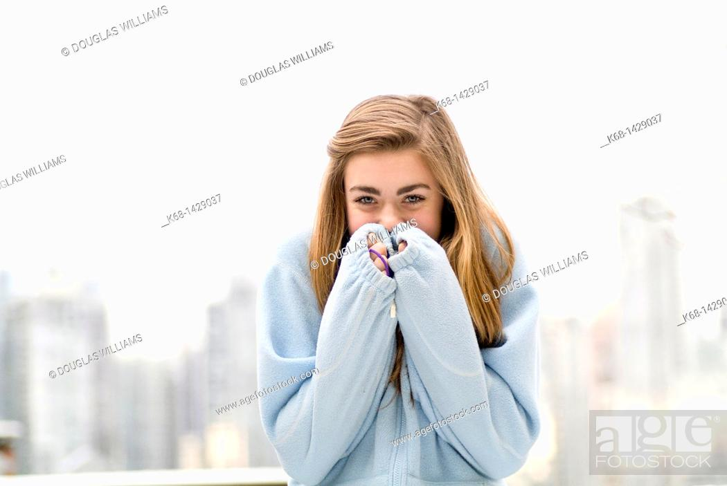 Stock Photo: a 15 year old girl, outdoors, covering her smile. Vancouver, BC, Canada, skyline in background.