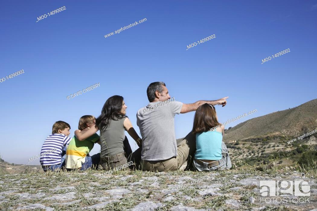 Stock Photo: Family with three children 7-12 sitting on mountain top back view.