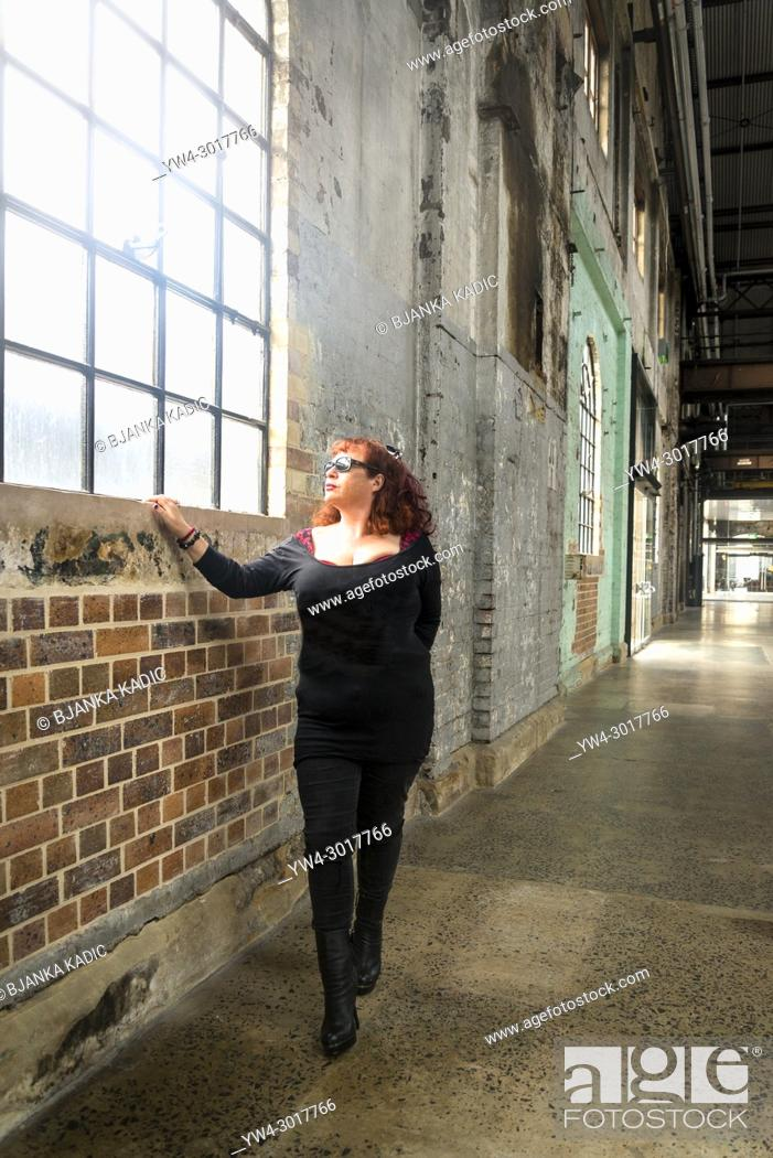 Stock Photo: Woman dressed in black looking through a window in an industrial type of building.