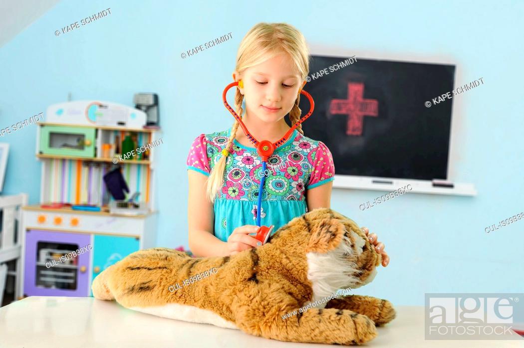 Stock Photo: Girl pretending to be vet examining toy tiger using stethoscope.