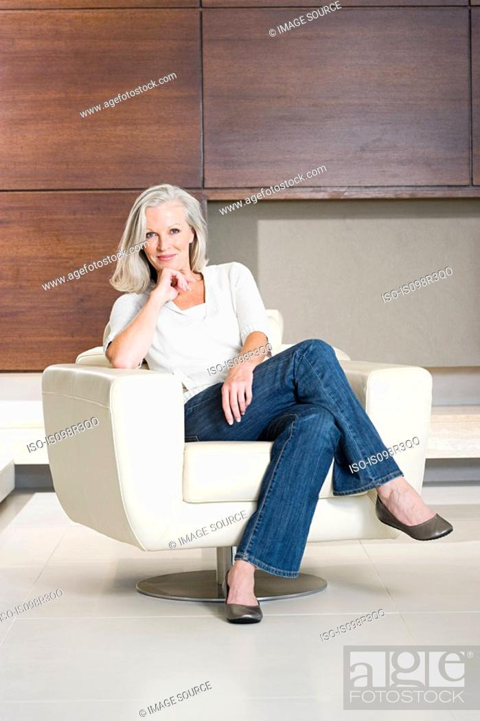 Stock Photo: Portrait of middle aged woman sitting on modern armchair.