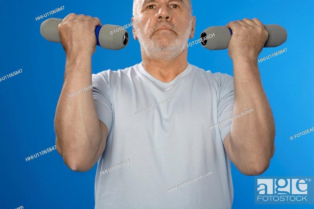 Stock Photo: Senior man training with dumbbells.