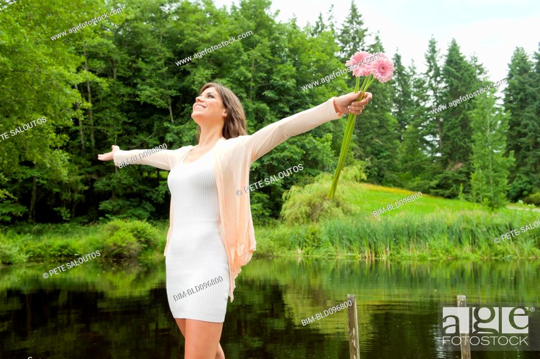 Stock Photo: Caucasian woman holding flowers near pond.