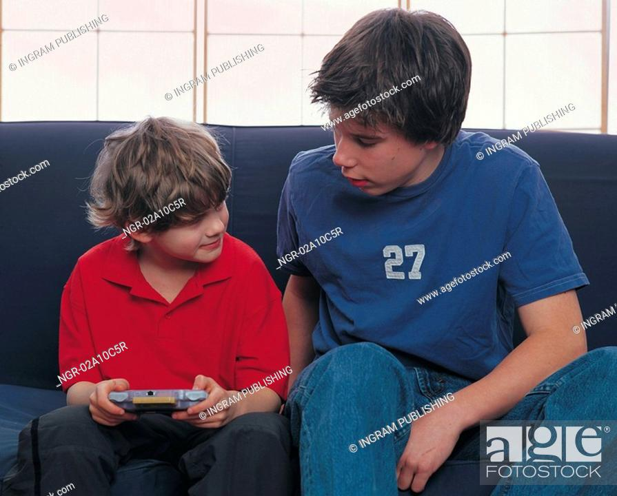 Stock Photo: two boys sharing a video game.