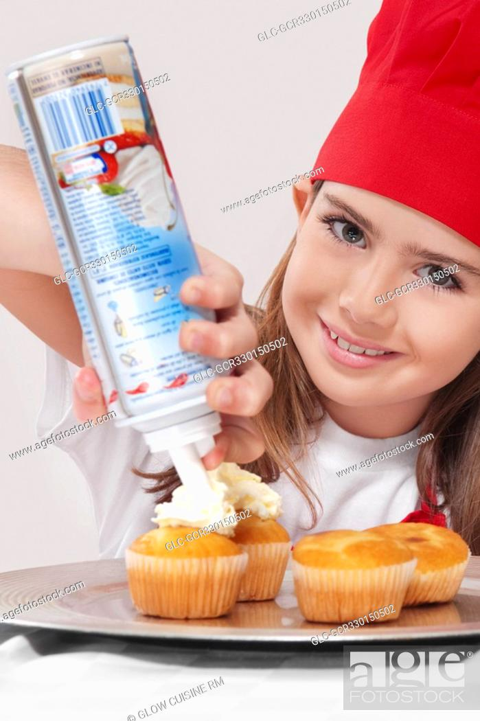 Stock Photo: Portrait of a girl putting whipped cream on cupcakes.