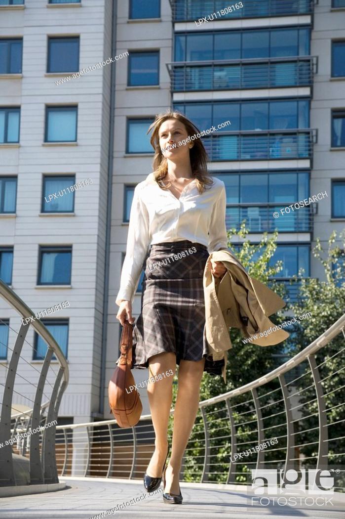Stock Photo: Businesswoman walking on bridge low angle view.