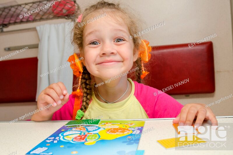 Stock Photo: Little girl on the train with a happy smile sitting at a table on the lower second-class place car and makes the applique.
