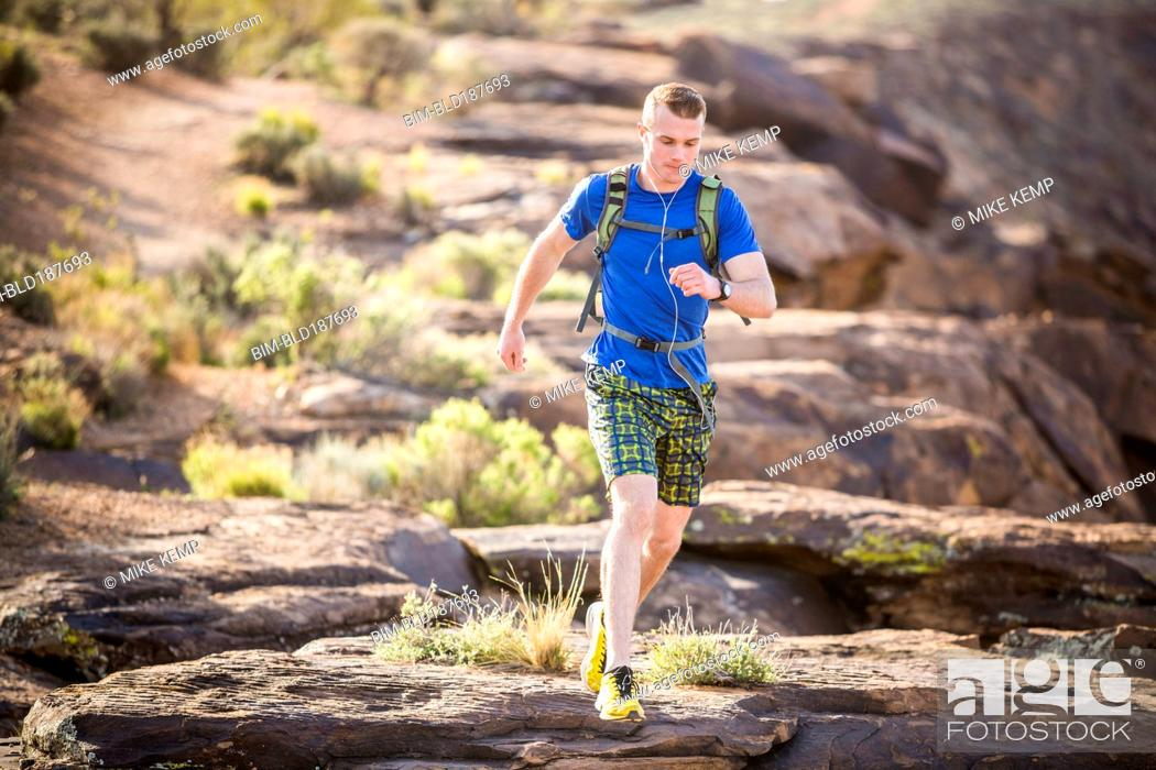 Imagen: Caucasian teenage boy running on rock formation.