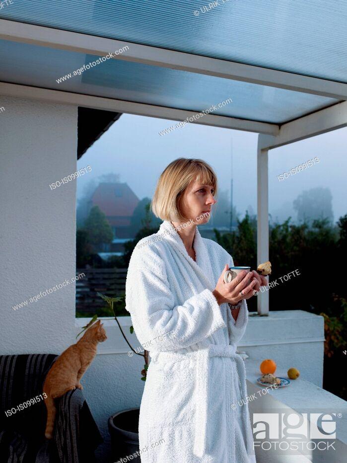 Stock Photo: Mature woman in bathrobe holding morning coffee on balcony.