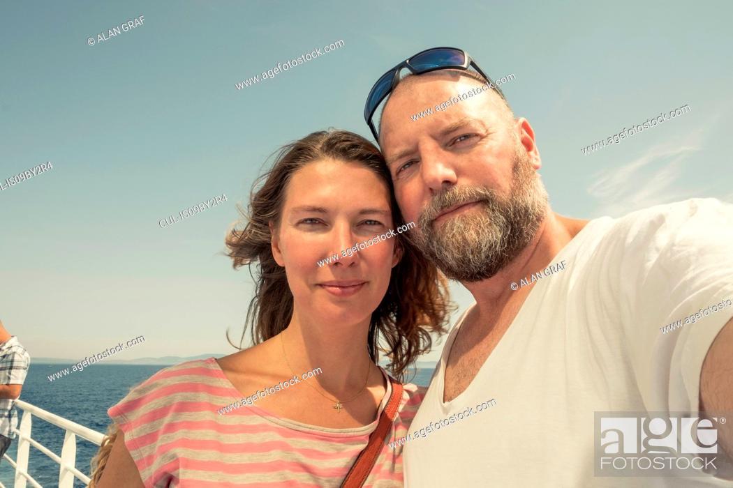 Stock Photo: Mature couple on pier, self portrait, Portoferraio, Tuscany, Italy.