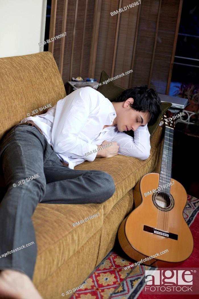 Imagen: Mixed race man sleeping on sofa next to guitar.