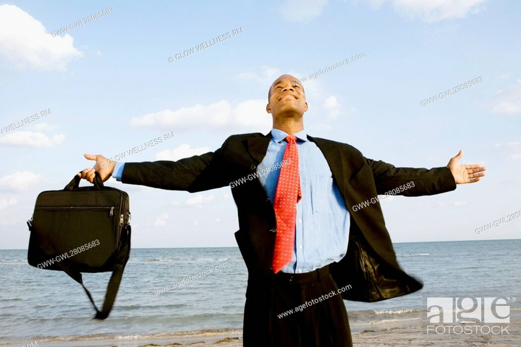 Imagen: Businessman standing on the beach with his arm outstretched.