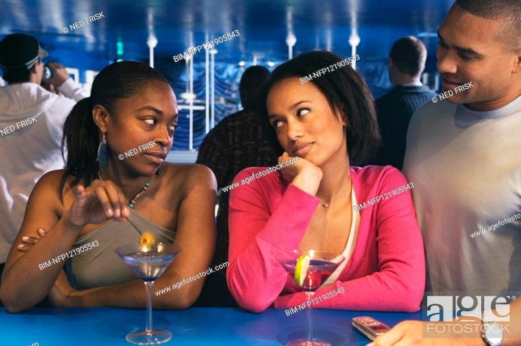 Stock Photo: Two African women looking at each other at bar.