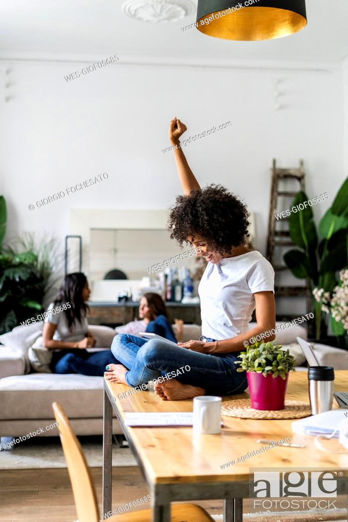 Stock Photo: Cheering woman using tablet on table at home with friends in background.