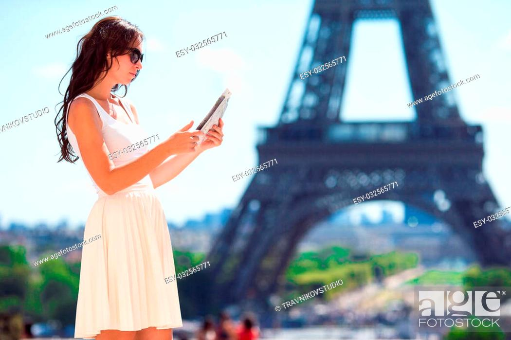Stock Photo: Happy young woman with a city map smiling riding on bicycle.