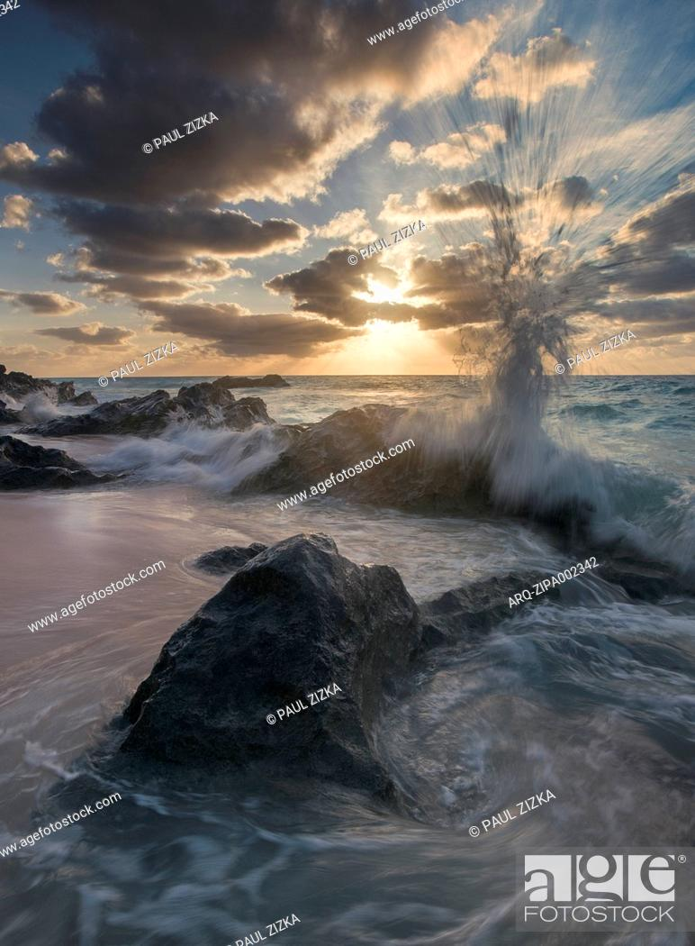 Imagen: Wave crashing on rocks at beach at sunset, Marley Beach, Bermuda.