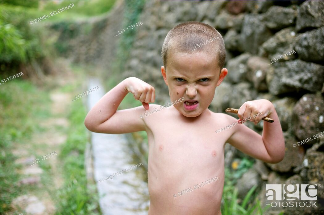 Stock Photo: boy with angry face showing muscles without T-shirt, Ludiente, Castellón, Spain.