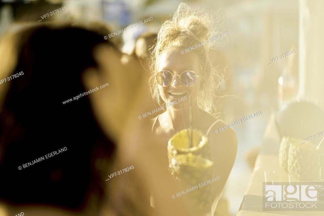 Stock Photo: Two women drinking cocktails at bar, Hersonissos, Crete, Greece.