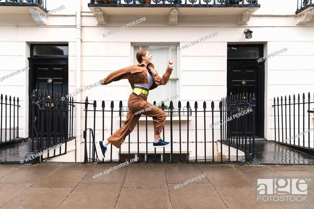 Stock Photo: Carefree young woman jumping in front of city houses, London, UK.