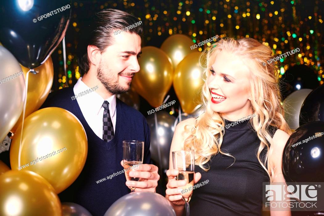 Stock Photo: Young man and woman at party, holding champagne glasses, smiling.