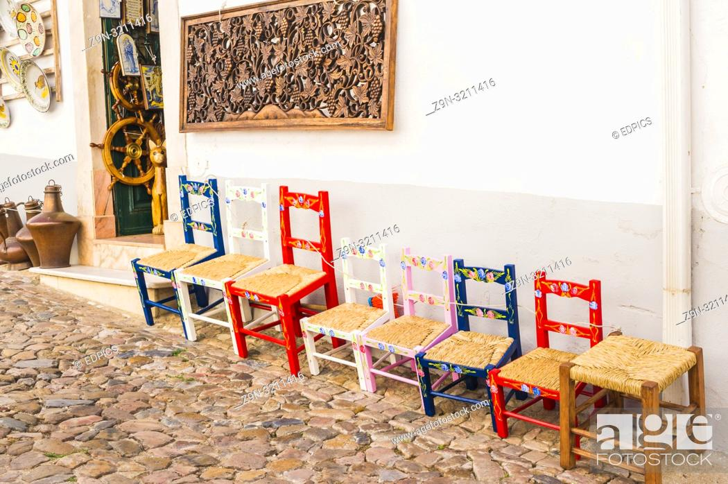Imagen: typical multicolored handcrafted chairs in front of a store selling local handicraft, estremoz, alentejo, portugal.