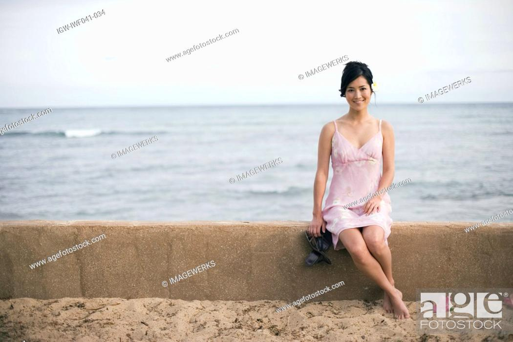 Stock Photo: A woman sitting on wall by sea.