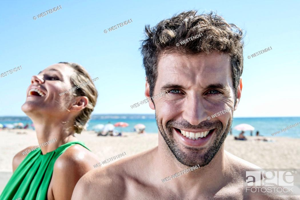 Stock Photo: Spain, Mid adult couple sitting at beach, smiling.