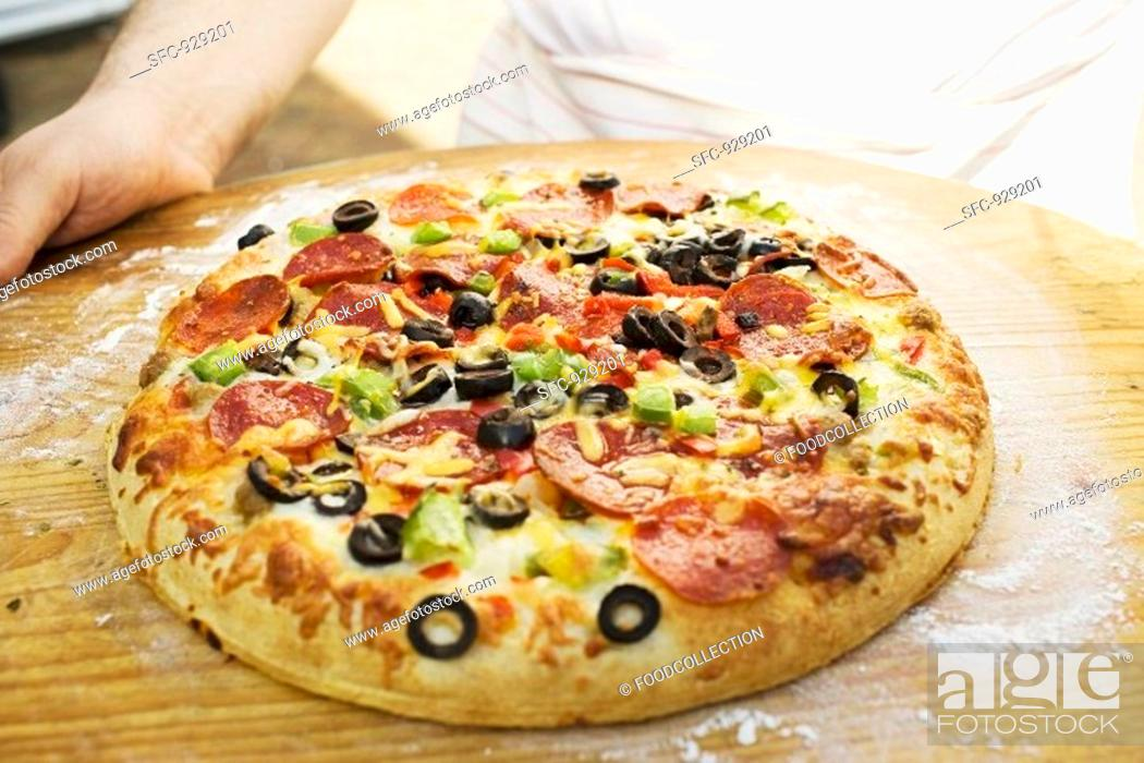 Stock Photo: Hands holding pepperoni pizza with peppers and olives.
